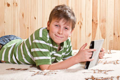 Adolescente del muchacho con el ordenador de la tablilla Fotografía de archivo