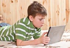 Adolescente del muchacho con el ordenador de la tablilla Imagen de archivo