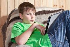 Adolescente del muchacho con el ordenador de la tablilla Fotos de archivo