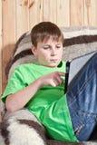 Adolescente del muchacho con el ordenador de la tablilla Fotografía de archivo libre de regalías