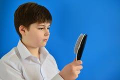Adolescente del muchacho con el peine en su mano Foto de archivo libre de regalías