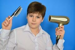 Adolescente del muchacho con el peine y un secador de pelo Foto de archivo