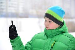 Adolescente del muchacho con el teléfono celular al aire libre en invierno Imágenes de archivo libres de regalías