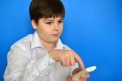 Adolescente del muchacho con la TV teledirigida en un fondo azul Imágenes de archivo libres de regalías