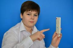 Adolescente del muchacho con la TV teledirigida en un fondo azul Foto de archivo