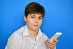 Adolescente del muchacho con la TV teledirigida en un fondo azul Fotos de archivo libres de regalías