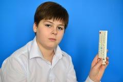 Adolescente del muchacho con la TV teledirigida en un fondo azul Imagenes de archivo
