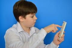 Adolescente del muchacho con la TV teledirigida en un fondo azul Fotografía de archivo libre de regalías