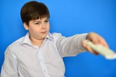 Adolescente del muchacho con la TV teledirigida en un fondo azul Imagen de archivo