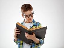 Adolescente del muchacho del niño con los vidrios reding el libro en fondo gris Foto de archivo