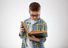 Adolescente del muchacho del niño con los vidrios reding el libro en fondo gris Imágenes de archivo libres de regalías