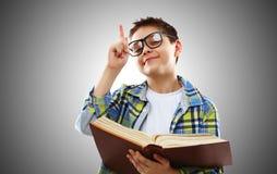 Adolescente del muchacho del niño con los vidrios y el libro Fotos de archivo libres de regalías