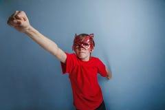 Adolescente del muchacho doce años en camisa roja en máscara Imágenes de archivo libres de regalías