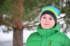 Adolescente del muchacho en chaqueta verde en el bosque del pino del invierno Fotografía de archivo libre de regalías