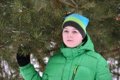 Adolescente del muchacho en chaqueta verde en el bosque del pino del invierno Imagenes de archivo