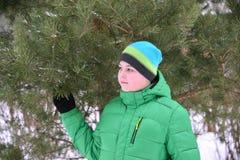 Adolescente del muchacho en chaqueta verde en el bosque del pino del invierno Imágenes de archivo libres de regalías