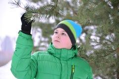 Adolescente del muchacho en chaqueta verde en el bosque del pino del invierno Fotografía de archivo