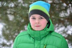 Adolescente del muchacho en chaqueta verde en el bosque del pino del invierno Fotos de archivo libres de regalías