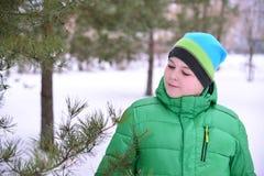 Adolescente del muchacho en chaqueta verde en el bosque del pino del invierno Imagen de archivo