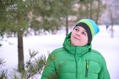 Adolescente del muchacho en chaqueta verde en el bosque del pino del invierno Fotos de archivo