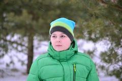 Adolescente del muchacho en chaqueta verde en el bosque del pino del invierno Imagen de archivo libre de regalías