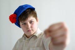 Adolescente del muchacho en el casquillo nacional ruso con los clavos que muestran un puño Foto de archivo libre de regalías