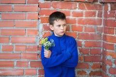 Adolescente del muchacho en un fondo de la pared de ladrillo Imágenes de archivo libres de regalías