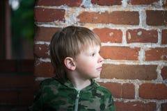 Adolescente del muchacho en un fondo de la pared de ladrillo Imagen de archivo libre de regalías