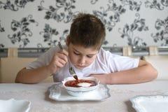 Adolescente del muchacho que come la sopa en la tabla de cocina Imagen de archivo libre de regalías