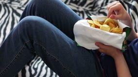 Adolescente del muchacho que come las patatas fritas con las manos en el sofá en casa comida malsana de los alimentos de preparac metrajes