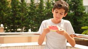 Adolescente del muchacho que come una sandía afuera en un fondo del verdor y del cielo Cámara lenta almacen de metraje de vídeo