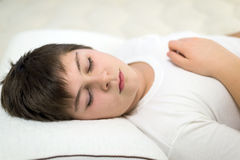 Adolescente del muchacho que duerme en la almohada anatómica Imagen de archivo libre de regalías