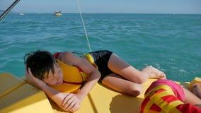Adolescente del muchacho que duerme en un barco en el mar adolescente del muchacho que descansa sobre un catamarán del barco del  almacen de video