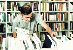 Adolescente del muchacho que elige el nuevo libro en tienda Imagenes de archivo