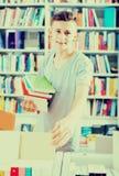 Adolescente del muchacho que elige el nuevo libro en tienda Foto de archivo libre de regalías