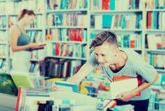 Adolescente del muchacho que elige el nuevo libro en tienda Imágenes de archivo libres de regalías