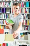 Adolescente del muchacho que elige el nuevo libro en tienda Fotografía de archivo