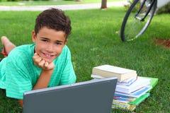 Adolescente del muchacho que estudia poniendo el jardín de la hierba verde Fotografía de archivo