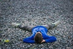 Adolescente del muchacho que miente en un sueño de la tiza Imagenes de archivo
