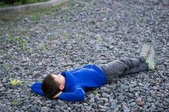 Adolescente del muchacho que miente en un sueño de la tiza Fotografía de archivo