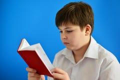 Adolescente del muchacho que mira en planificador del día Fotografía de archivo libre de regalías