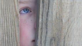 Adolescente del muchacho que mira a escondidas en la grieta en cerca o entrada almacen de video