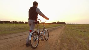 Adolescente del muchacho que monta una bici en un camino en naturaleza adolescente del muchacho que viaja en bici del aire libre almacen de video