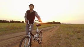 Adolescente del muchacho que monta una bici en un camino en naturaleza adolescente del muchacho que viaja al aire libre en bici metrajes