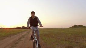 Adolescente del muchacho que monta una bici en un camino en naturaleza adolescente del muchacho que viaja en bici al aire libre almacen de metraje de vídeo