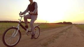 Adolescente del muchacho que monta una bicicleta El adolescente del muchacho que monta una bicicleta va a la naturaleza a lo larg almacen de video