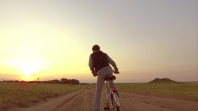 Adolescente del muchacho que monta una bicicleta El adolescente del muchacho que monta una bicicleta va a la naturaleza a lo larg Imágenes de archivo libres de regalías