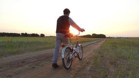 Adolescente del muchacho que monta una bicicleta La bicicleta del montar a caballo del adolescente del muchacho va naturaleza a l almacen de video