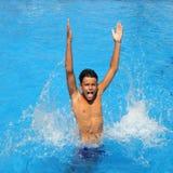 Adolescente del muchacho que salpica la piscina abierta de los brazos del agua Imagenes de archivo
