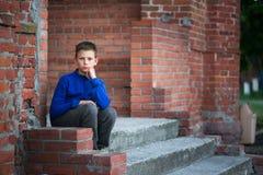 Adolescente del muchacho que se sienta en el pórtico en casa Imagen de archivo libre de regalías